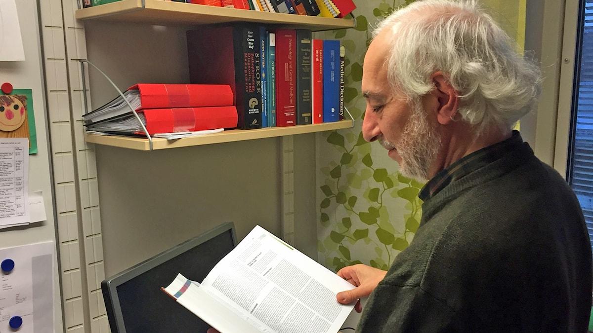 Professor Turgut Tatlisumak läser en bok vid en bokhylla