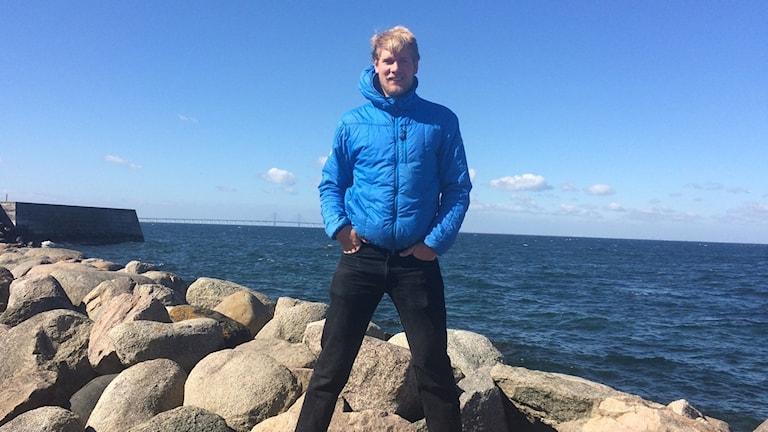 Max Salminen seisoo rantakivillä veden tuntumassa sininen toppatakki päällään.