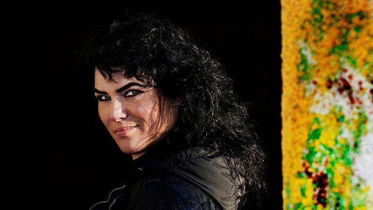 Eija Hetekivi Olsson en kvinna med mörkt hår med svart bakgrund och färgglad pelare till höger