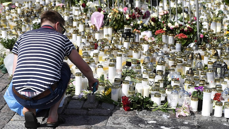 Kuvassa mies sytyttää kynttilän Turun puukotusiskun uhreille.