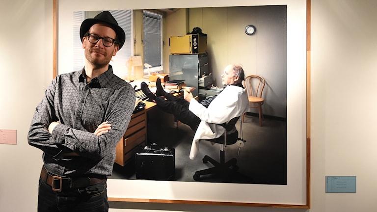 Ville Lenkkeri seisoo kädet puuskassa ja hattu päässään isästä ottamansa valokuvan edessä.
