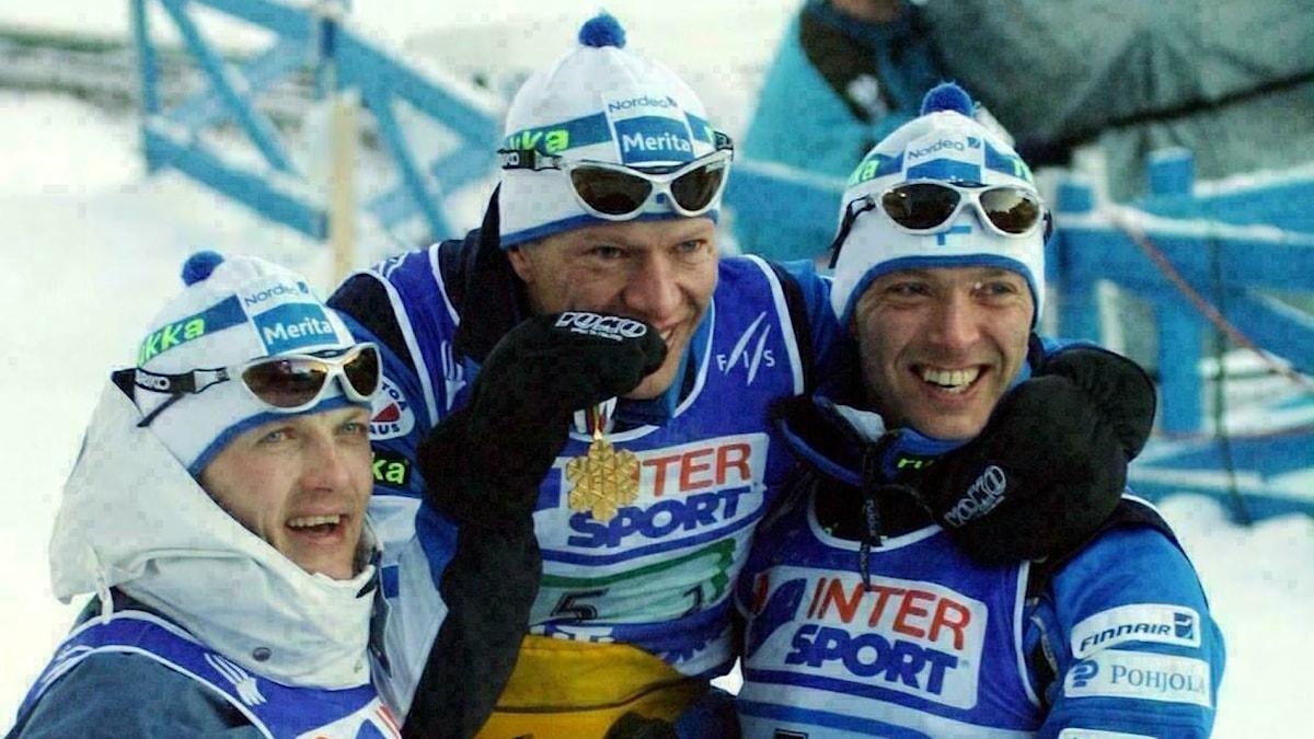 Kuvassa näkyy Suomen hiihtomaajoukkueen hiihtäjät Janne Immonen, Harri Kirvesniemi ja Mika Myllylä vuonna 2001 juhlimassa kultamitalleitaan. Kuva: Matti Björkman/TT Bild