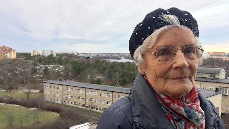 Eeva Servelius parvekkellaan, josta näkymä Årstan lahdelle ja Södermalmille Tukholmassa.