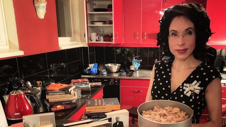 Författaren Sofi Oksanen står i ett rött kök med böcker och mat