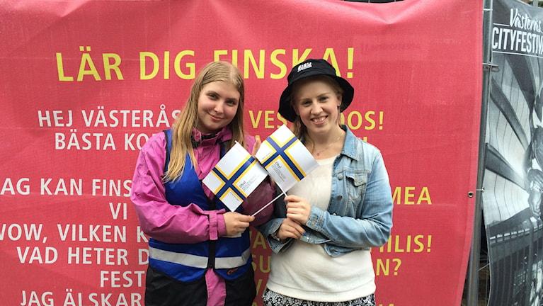 Alva Harju Jansson ja Erika Strandman pitävät ruotsinsuomalaisten lipusta ja suomen kielestä.