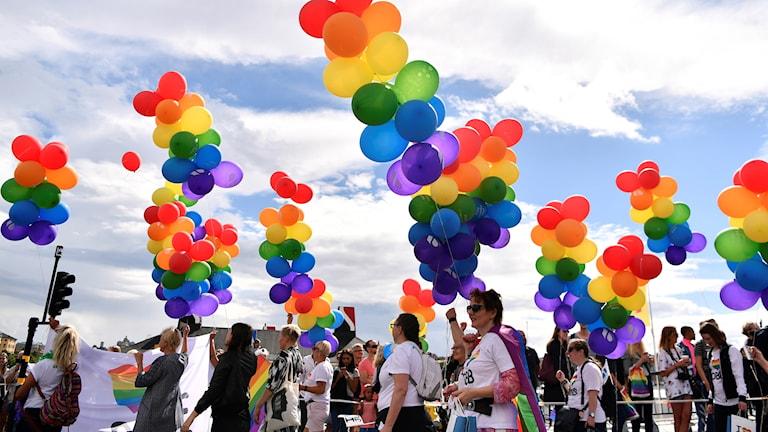 Ihmiset marssivat Pride-paraatilla Tukholmassa