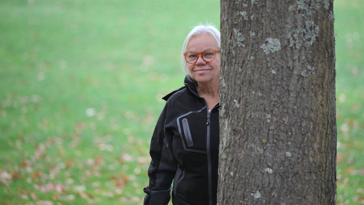 Entinen opettaja Irmeli Pulli kurkistaa puun takaa. Hänellä on vaaleat hiukset ja punaiset silmälasit, sekä musta takki. Irmeli hymyilee.