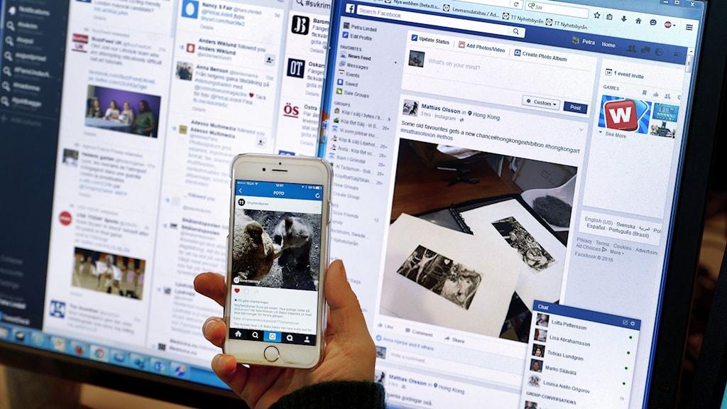 Näyttöpääte ja kännykkä, jossa avattuna sosiaalisen median sivuja.