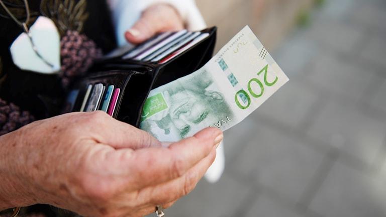 Naisen käsi ottaa rahaa lompakosta