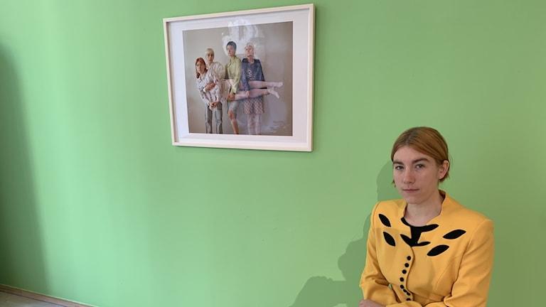 Keltavaatteinen Sarpaniemi istuu yhden valokuvansa vieressa, taustallaan vihreä seinä. Kuva: Timo Laine/Sveriges Radio