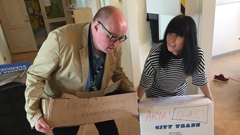 Hanna ja Jorma kantavat muuttolaatikoita