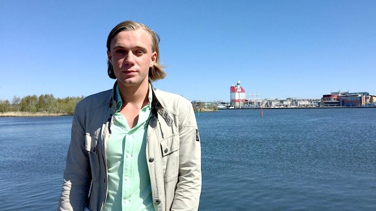 En blond ung manstår vid strandkanten