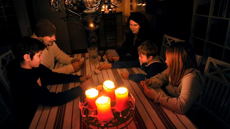 Kuvassa perhe on kokoontunut pöydän ympärille pimeässä huoneessa, ja sytyttänyt kynttilöitä.