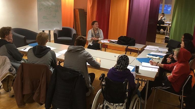 Nyeportin vapaa-ajantalon suomen opiskelua Skövdessä, 7 nuorta pöydän ympärillä, taustalla opettajansa Taru Fogelström