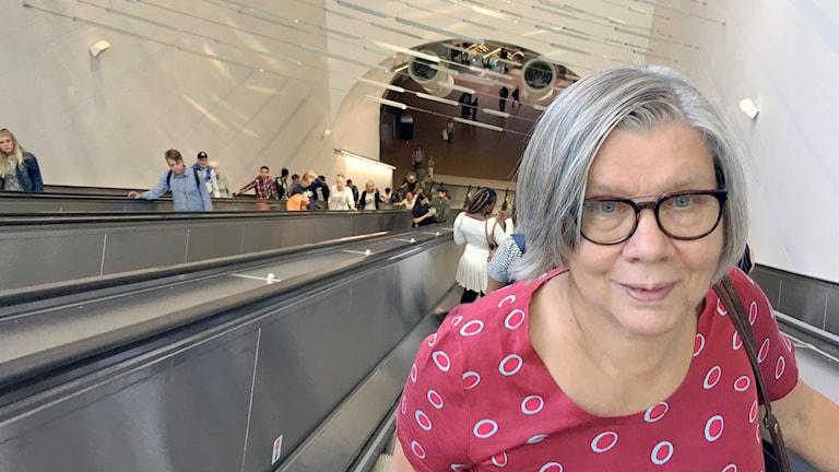 Liisa Paavilaisen taustalla näkyy eteläisen uloskäynnin rullaportaat. Kuva: Riitta Niemi/Sveriges Radio Sisuradio