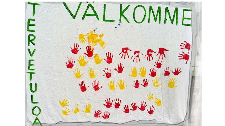 Iso lippu, jossa lukee tervetuloa ja välkommen ja on värikkäitä kädenjälkiä