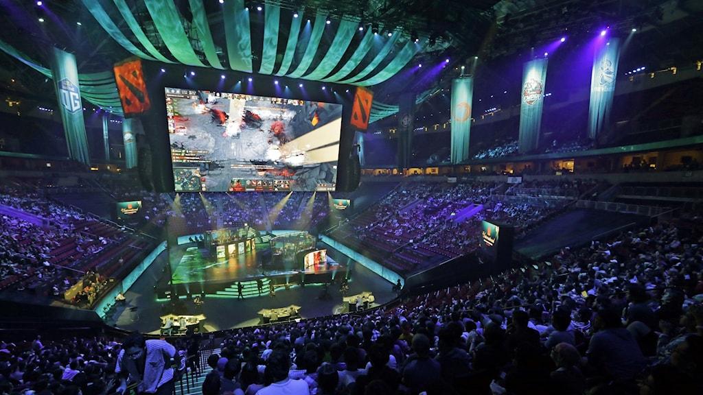Täysi areena Dota 2 -mestaruuskilpailuissa, jossa keskellä pelaajat ja iso näyttö, josta yleisö voi seurata peliä. Kuva: Elaine Thompson/AP