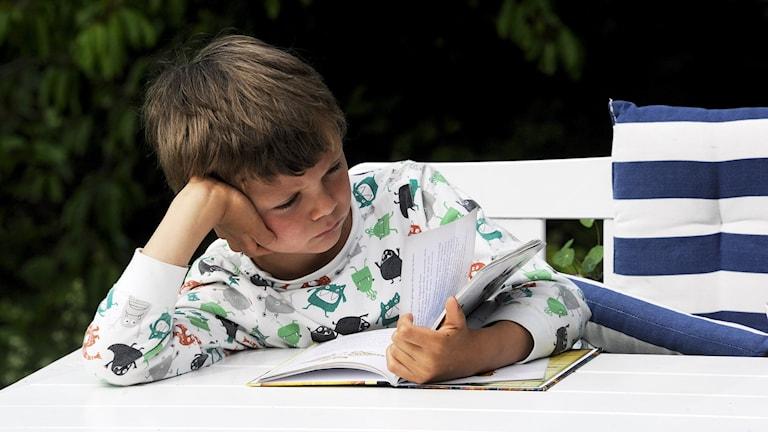 Lapsi lukee kirjaa valkoisen pöydän ääressä.