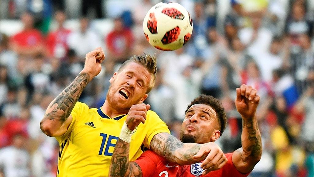 Ruotsin Pontus Jansson ja Englannin Kyle Walker taistelevat pallosta jalkapallon MM-kisojen välieräottelussa.