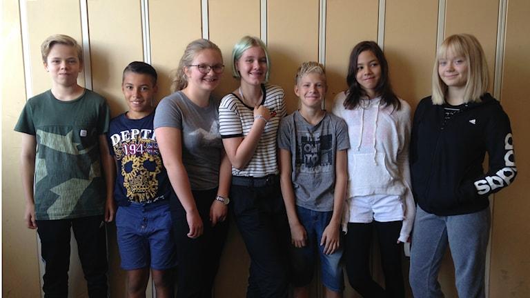 Tukholman Ruotsinsuomalaisen koulun kutosluokkalaiset, kolme poikaa ja neljä tyttöä, seisovat rivissä koulun käytävässä. Kaikki katsovat kameraan ja näyttävät iloisilta.