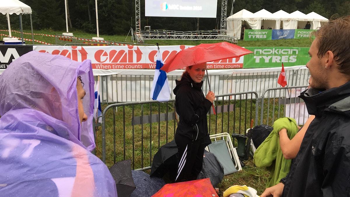 Sateinen suunnistuksen maalialue, Janina Donner varjonsa alla Suomen lippujen vieressä