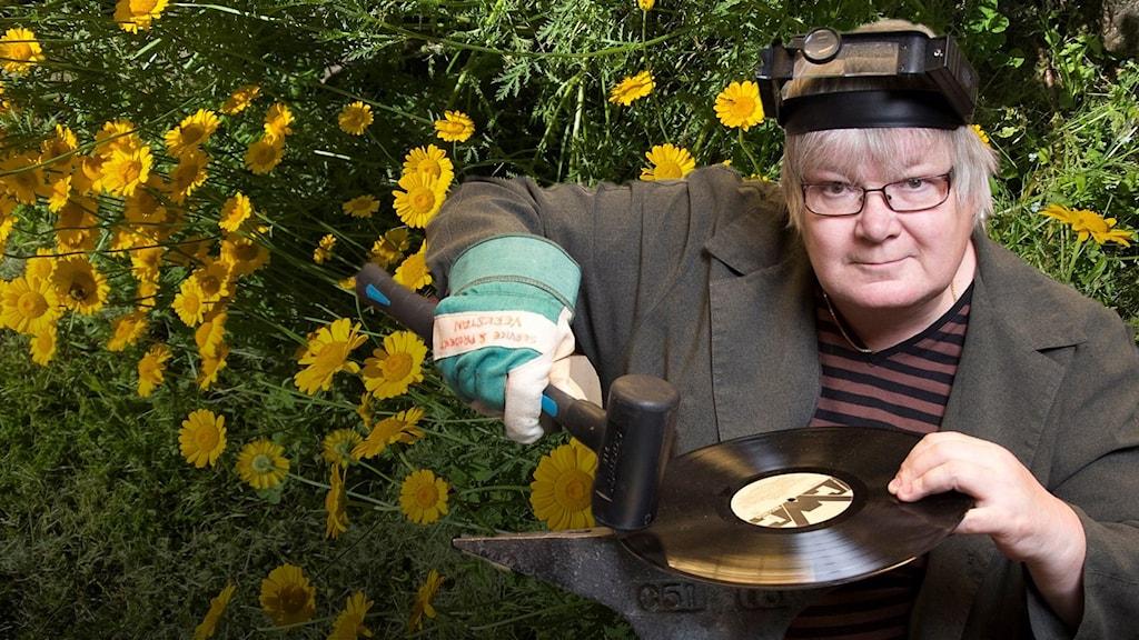 Keltaisia kukkia, keltasauramoita taka-alalla, Pirjo Rajalakso etuallalla sepän varusteissa ja lp-levy kädessä.