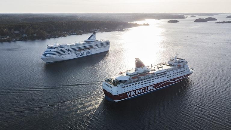 Två finlandsfärjor fotograferade ovanifrån seglar i motsatt riktning. Till vänster i bild syns land och i bakgrunden skärgårdsöar.