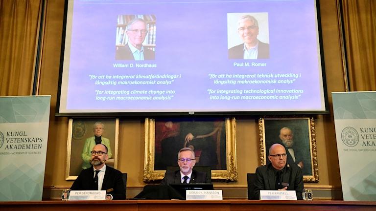 Kolme miestä ilmoittavat taustalla näkyvien tutkijoiden saavan palkinnon.