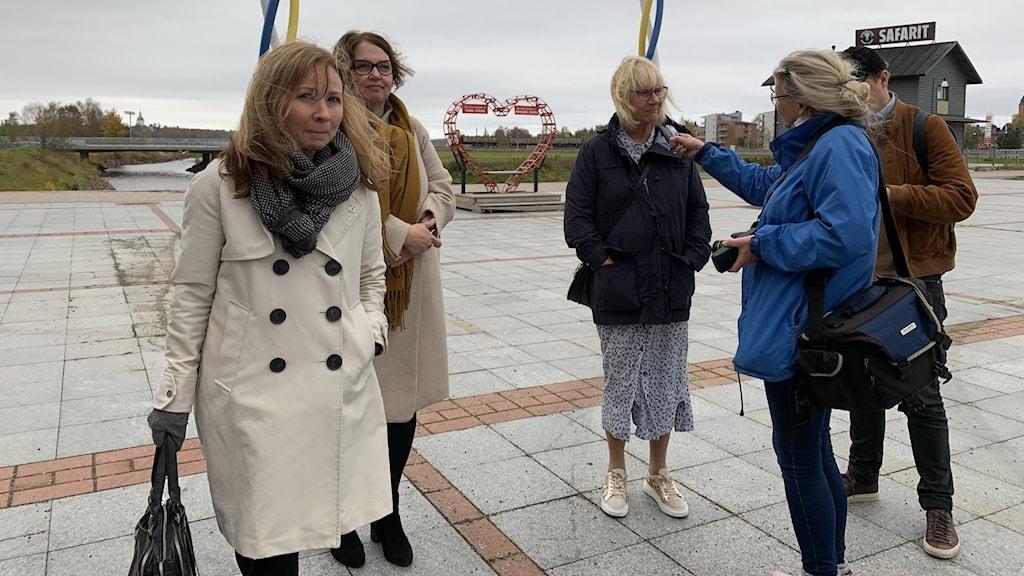 Viisi henkilöä seisomassa torilla kylmässä syystuulessa.
