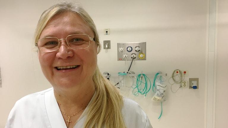 Sairaalaasuinen hymyilevä Oili Piippo Huotari sairaalan hoitohuoneessa.
