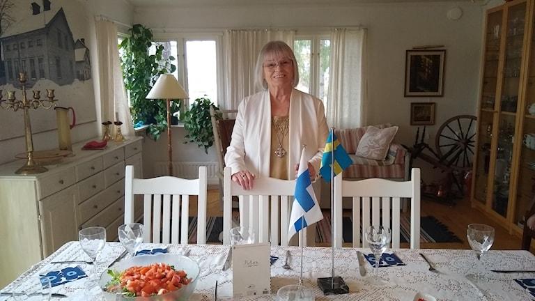 Irja Olsson kotonaan pöydän vieressä.