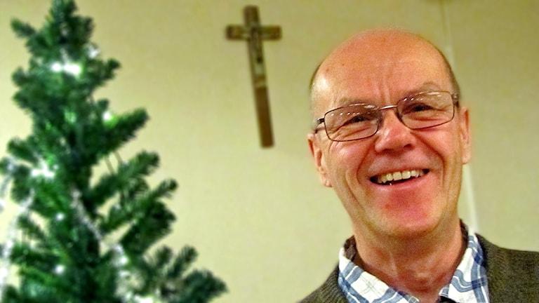 Keski-ikäinen, silmälasipäinen mies lähikuvassa sisätiloissa taustallaan joulukuusi ja pienoiskrusifiksi seinällä.