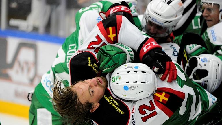 Kuvassa Malmö Redhawks -joukkueen kypäränsä pudottanut jääkiekkoilija on joutunut Röglen pelaajien pursitukeen. Malmön pelaaja näyttää hätääntyneeltä, Röglen pelaajat puolestaan vihaisilta.