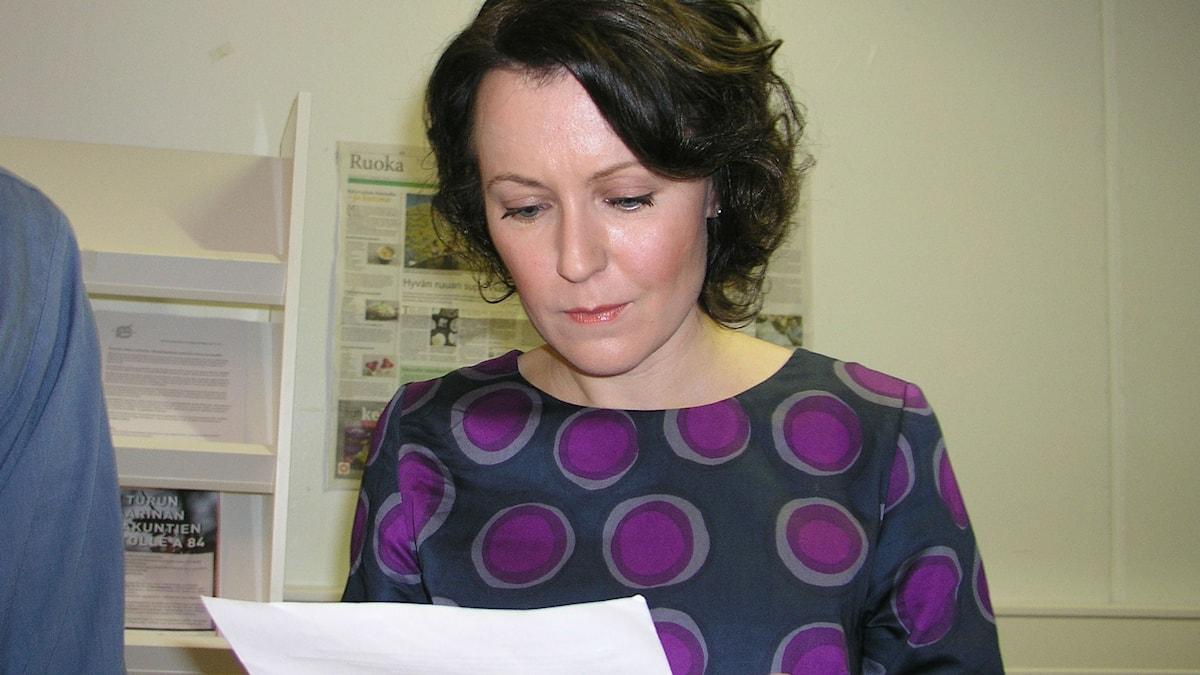 Jenni Haukio lukee paperia pallokuvioisessa puserossaan
