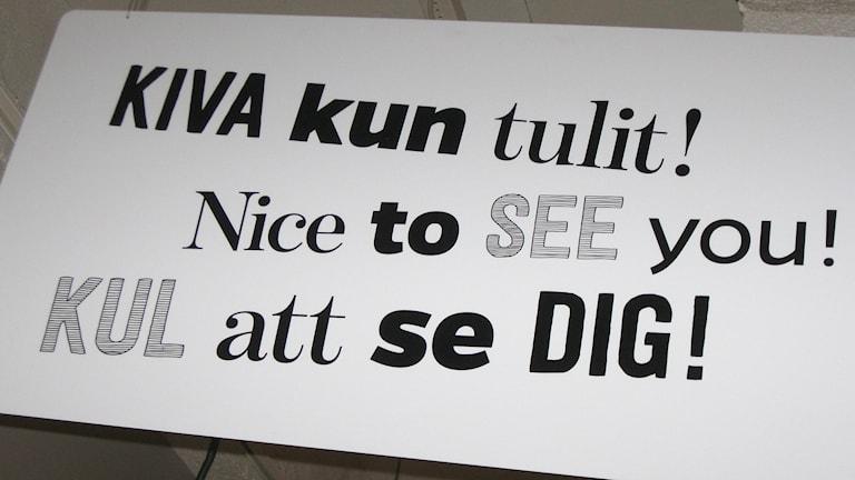 Tekstiilimuseon tervetulleeksi toivottava kolmikielinen kyltti. Kuva: Teija Martinsson.