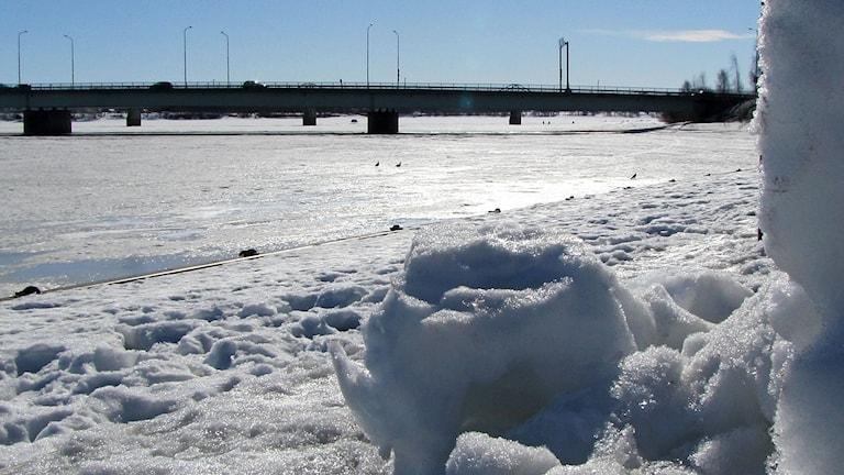 Kevättalvinen Tornionjoki jäässä ja taustalla näkyy maantiesilta auringonpaisteessa.