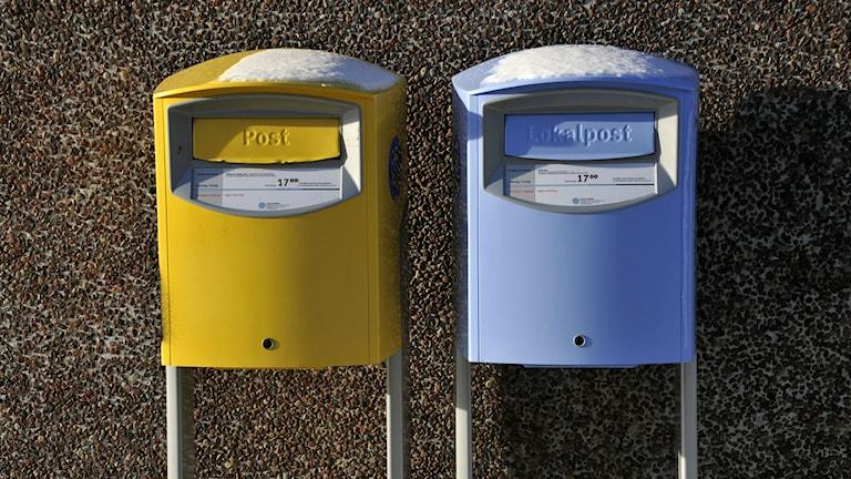 Keltainen ja sininen postilaatikko.