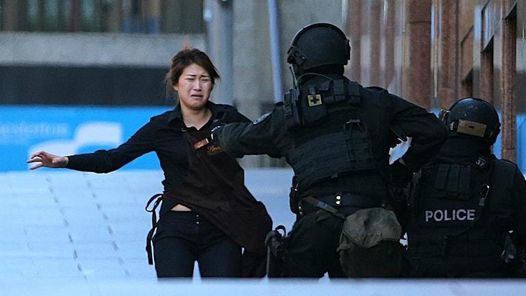 Panttivanki onnistuu pakenemaan kahvilasta ja juoksee poliisin luo. AP Photo/Rob Griffith.