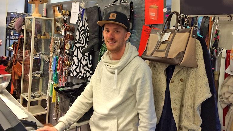 Oliver työskentelee hyväntekeväisyysjärjestön ylläpitämälla kirpputorilla ja sanoo, että joululahjoiksi ostettujen tavaroiden avokauppa on voimassa ensi vuoden alkuun asti. Foto: Virpi Inkeri/SR