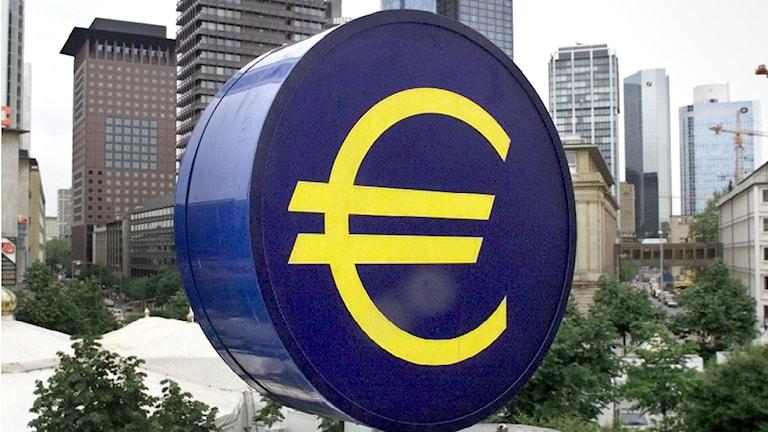 Euro-kello kerrostalojen edessä.
