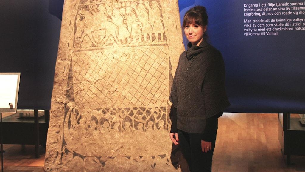 Arkivaari Kerstin Näversköld seisoo riimukiven vieressä