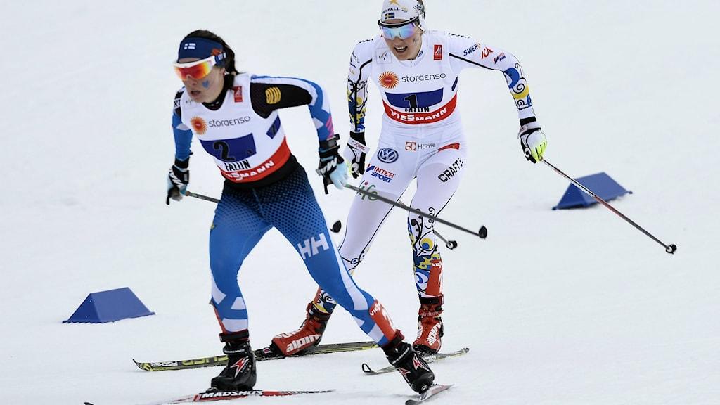 Suomen Krista Pärmäkoski ja Ruotsin Stina Nilsson hiihtävät naisten viestiä Falunissa . Foto: Anders Wiklund/TT.