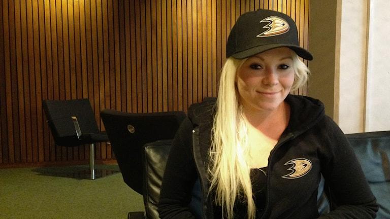 Anaheim Ducks -fani Johanna Lappalainen joukkueen fanihuppari ja -lippis yllään.
