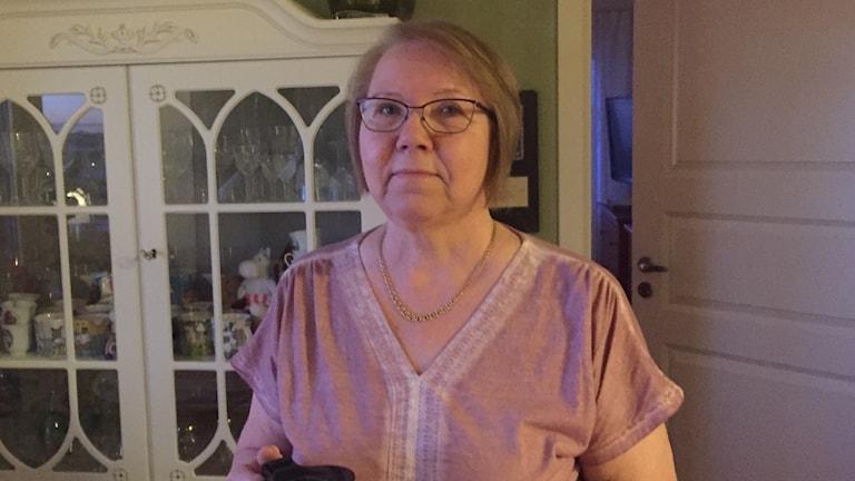 Vaalean marjapuuron väriseen asuun pukeutunut Sirkka-Liisa seisoo vitriinikaapin edessä.