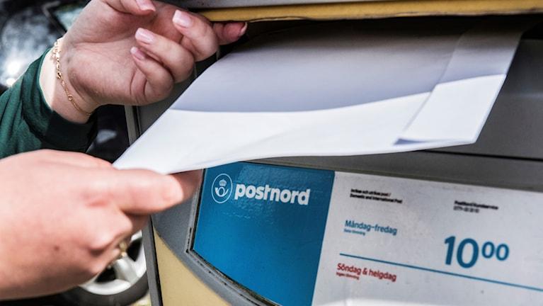 på bilden lägger en person brev i en postlåda.