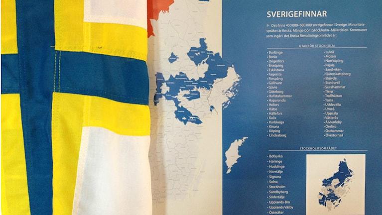 Ruotsinsuomalaisten lippu hallintoaluekartan edessä. Foto: Elina Härmä, Sisuradio