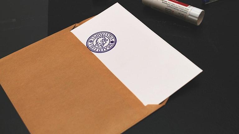 Ruskea kirjekuori, siitä pilkoittaa äänestysseteli, jossa virallinen vaalileima