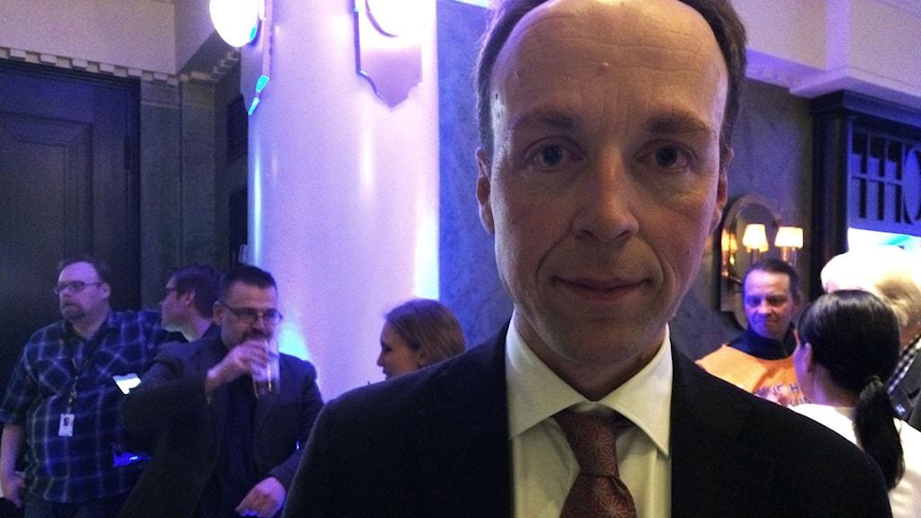 Jussilla on puku ja solmio, taustalla liilanvaloista vaalivalvojaista