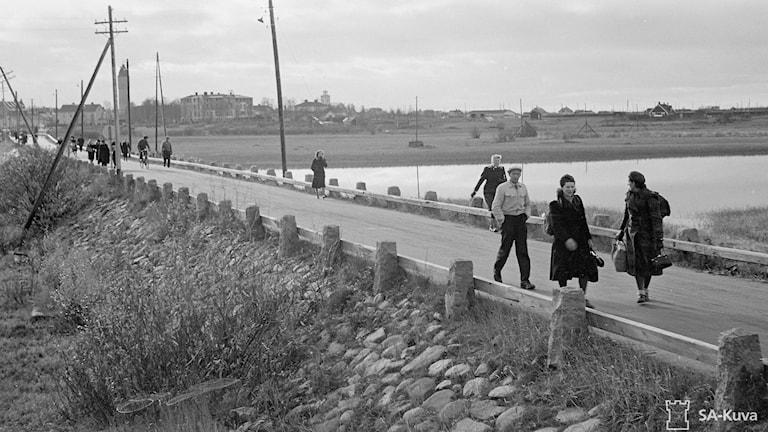 Rintaman siirryttyä palaavat siviiliasukkaat kotiinsa Tornioon Haaparannasta, joka näkyvissä taustalla. Tornio 1944.10.09. Lähde/Källa: SA-kuva. Valokuvaaja/Fotograf: Sot.virk. A.Viitasalo. Kuvan nro: 165605.