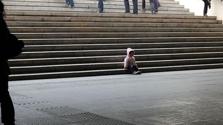 Pieni lapsi istuu huppu päässä ja yksin rappusilla